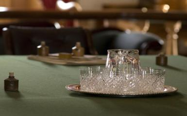 An image of water glasses on a green tablecloth