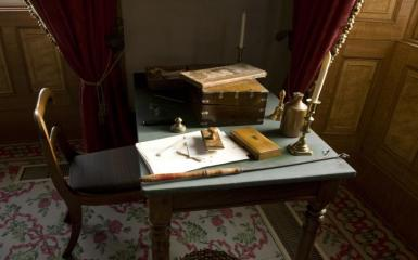 An image of an antique desk with papers on it