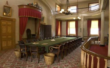 An image of the Confederation Chamber in Province House, with a chair on a dais and a long table covered with a green cloth