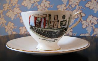 A photo of a china teacup and saucer printed with a colour sketch of the Confederation Chamber.